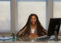 Black businesswoman sitting at desk with hands clasped and long braided hair. The woman is wearing glasses and smiling at the camera.